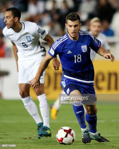 Cyprus' midfielder Kostakis Artymatas runs with the ball past Greece's midfielder Zeca during their World Cup 2018 qualifying Group H football match...