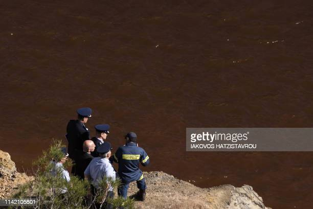 Cyprus police chief Kypros Michaelides is briefed by fire department chief Marcos Trangolas at the acidic Red Lake near the village of Mitsero...