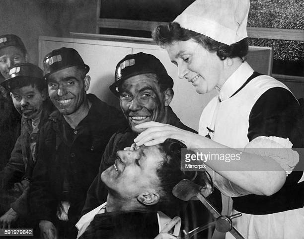 Cyril Annisworth a 16 years old screen worker bites his lip as sister Ada swabs out his eye which had been covered with coal dust His mates who are...