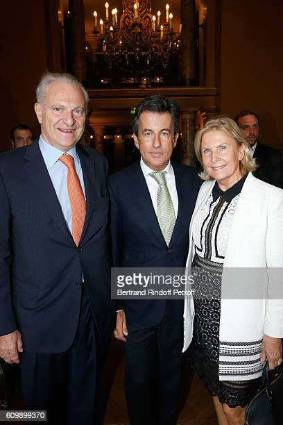 Cyril Karaoglan standing between Alain Flammarion and his wife Suzanna attend Cyril Karaoglan receives the Medal of Commander of Arts and Letters at...