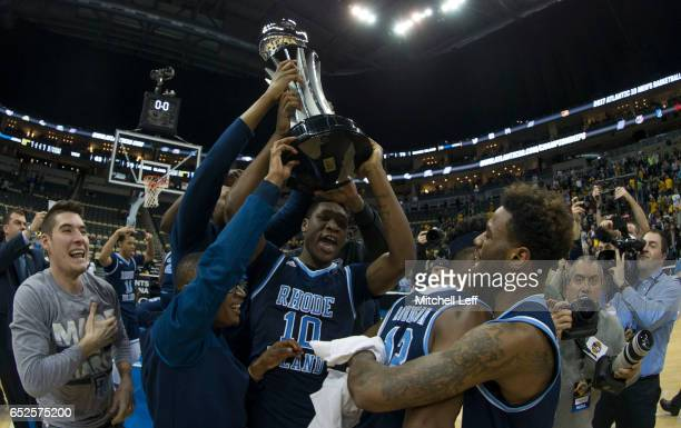 Cyril Langevine of the Rhode Island Rams holds up the trophy after the game against the Virginia Commonwealth Rams in the Championship game of the...
