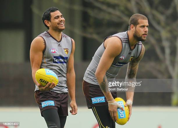 Cyril Rioli laughs as Lance Franklin prepares to kick the ball during a Hawthorn Hawks AFL training session at Waverley Park on September 17, 2013 in...