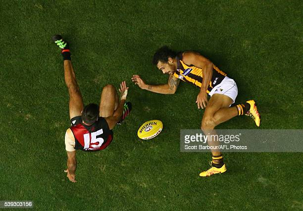 Cyril Rioli of the Hawks and Courtenay Dempsey of the Bombers compete for the ball during the round 12 AFL match between the Essendon Bombers and the...