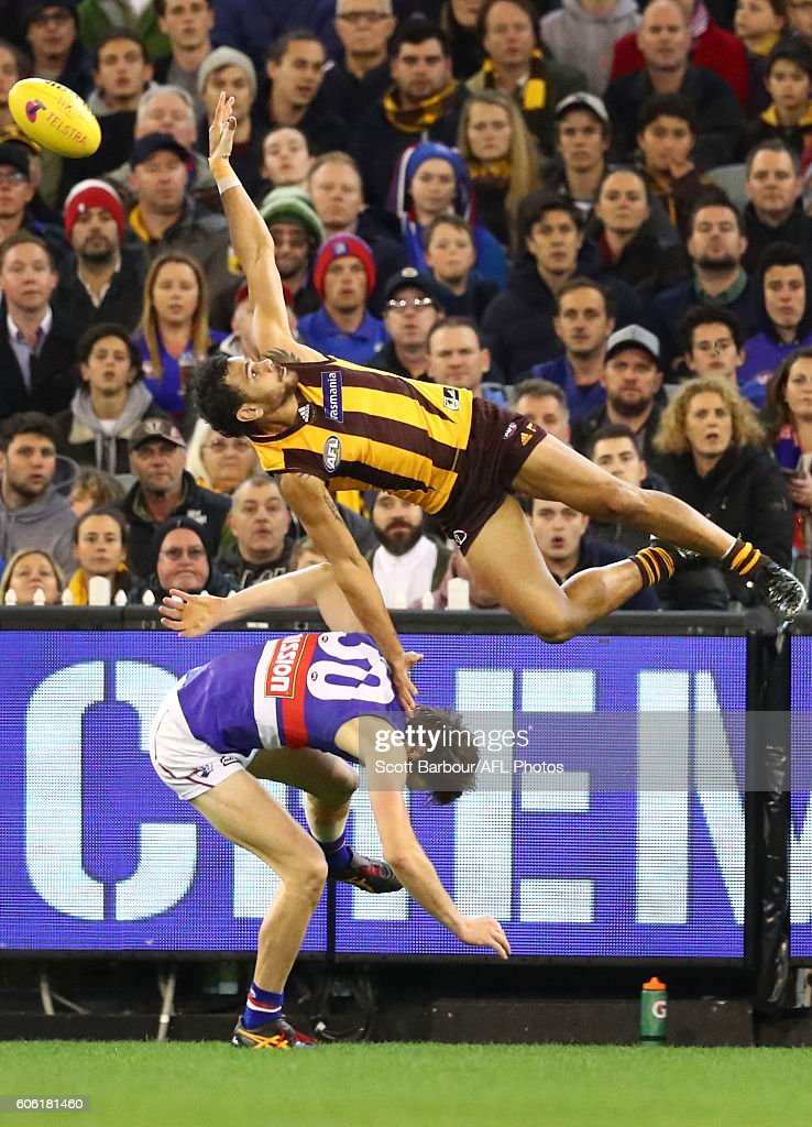Cyril Rioli of the Hawks attempts to take a spectacular mark over Joel Hamling of the Bulldogs during the second AFL semi final between Hawthorn Hawks and Western Bulldogs at Melbourne Cricket Ground on September 16, 2016 in Melbourne, Australia.