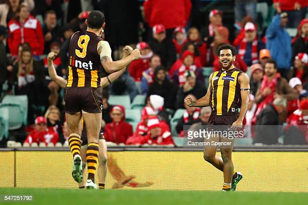 Cyril Rioli of the Hawks celebrates with team mate Shaun Burgoyne after winning the round 17 AFL match between the Sydney Swans and the Hawthorn...