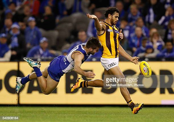 Cyril Rioli of the Hawks is tackled by Luke McDonald of the Kangaroos during the 2016 AFL Round 13 match between the North Melbourne Kangaroos and...