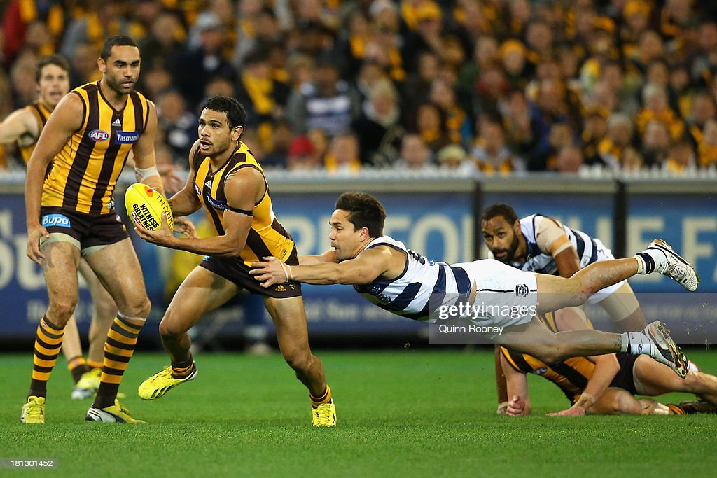 Cyril Rioli of the Hawks is tackled by Mathew Stokes of the Cats during the AFL First Preliminary Final match between the Hawthorn Hawks and the Geelong Cats at Melbourne Cricket Ground on September 20, 2013 in Melbourne, Australia.
