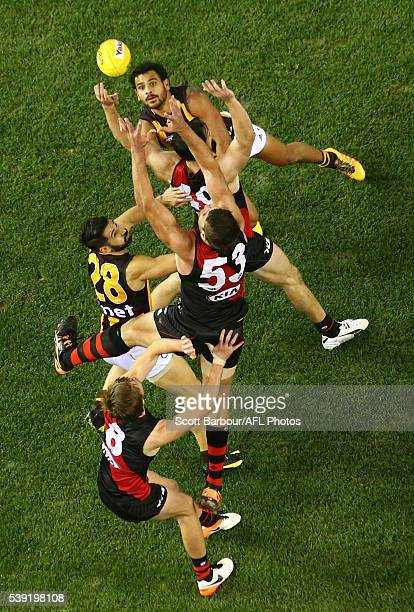 Cyril Rioli of the Hawks Mark Jamar of the Bombers and Paul Puopolo of the Hawks compete for the ball during the round 12 AFL match between the...