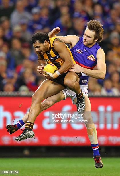 Cyril Rioli of the Hawks marks the ball against Joel Hamling of the Bulldogs and kicks a goal during the second AFL semi final between Hawthorn Hawks...