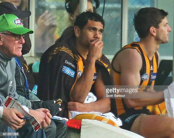 Cyril Rioli of the Hawks sits on the bench after he injured his hamstring during the round 15 AFL match between the Hawthorn Hawks and the Gold Coast...