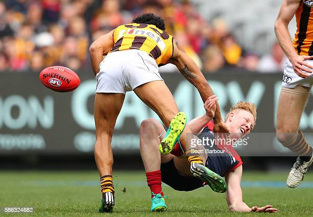 Cyril Rioli of the Hawks tackles Clayton Oliver of the Demons in a big high tackle during the round 20 AFL match between the Melbourne Demons and the...
