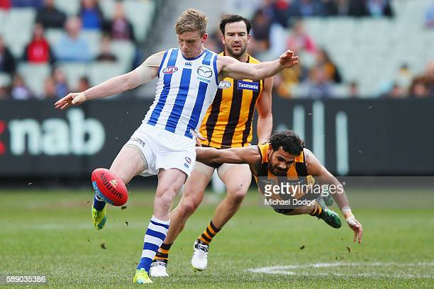 Cyril Rioli of the Hawks tackles Jack Ziebell of the Kangaroos as he kicks the ball during the round 21 AFL match between the Hawthorn Hawks and the...