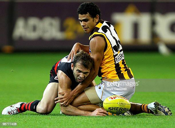 Cyril Rioli of the Hawks tackles Mark McVeigh of the Bombers during the 6 AFL match between the Essendon Bombers and the Hawthorn Hawks at Melbourne...