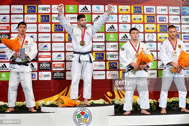 Cyrille Maret of France raises his arms to celebrate receiving the u100kg gold medal alongside The other medallists silver medallist Kyle Reyes of...