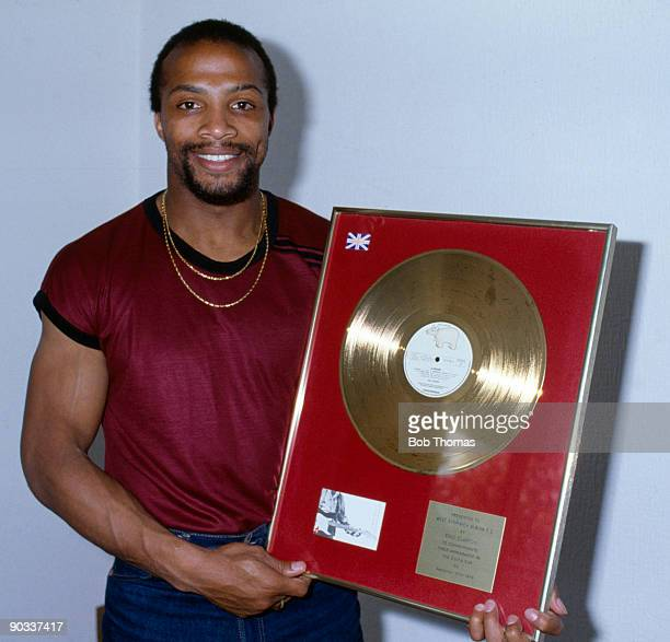 Cyrille Regis of West Bromwich Albion holding a framed gold record disc given to him by musician Eric Clapton circa 1982