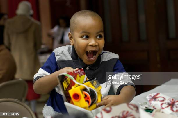 Cyrus Bishop age six opens a gift during a Christmas dinner hosted by Engine 277 Ladder 112 of the Fire Department of New York on December 25 2011 in...