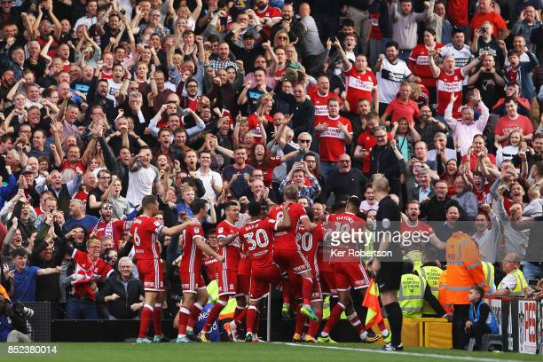 Cyrus Christie of Middlesbrough is surrounded by celebrating team mates after his late equaliser during the Sky Bet Championship match between Fulham...