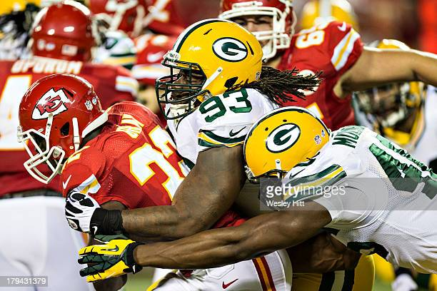 Cyrus Gray of the Kansas City Chiefs is tackled by Josh Boyd and Andy Mulumba of the Green Bay Packers during the last preseason game at Arrowhead...