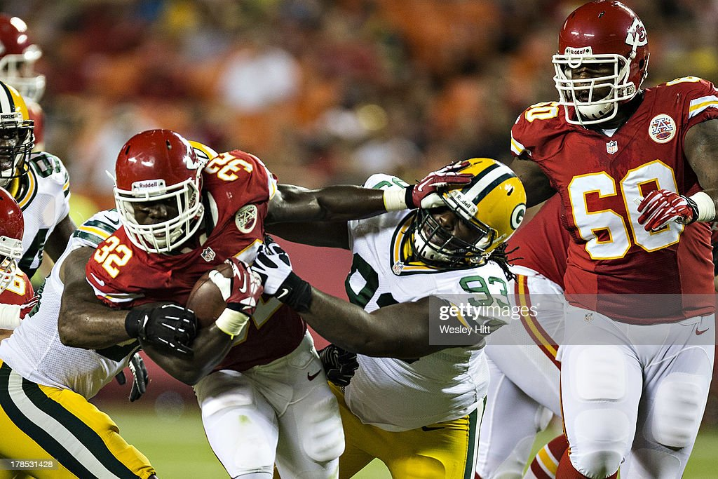 Cyrus Gray #32 of the Kansas City Chiefs stiff arms Josh Boyd #93 of the Green Bay Packers during the last preseason game at Arrowhead Stadium on August 29, 2013 in Kansas CIty, Missouri.