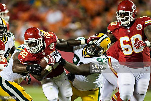Cyrus Gray of the Kansas City Chiefs stiff arms Josh Boyd of the Green Bay Packers during the last preseason game at Arrowhead Stadium on August 29...
