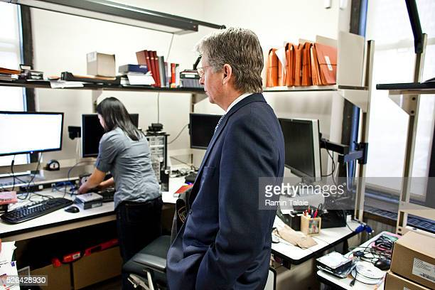 Cyrus R Vance Manhattan District Attorney looks on as an unidentified analyst works on a computer in the DA's cyber crime lab in Lower Manhattan in...