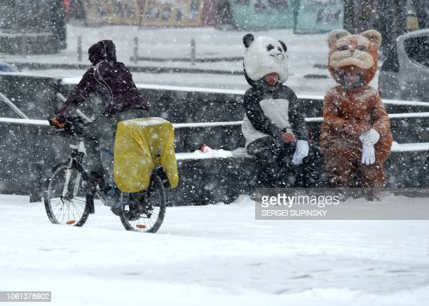 TOPSHOT A cyslist rides past people wearing animal costumes during heavy snowfall the first in the autumn in the centre Kiev on November 14 2018