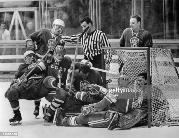 Czech and Soviet ice hockey players are tangled in front of the Czech goal cage as the referee stops the play 15 February 1968 in Grenoble during the...