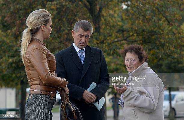 Czech billionaire Andrej Babis chairman of the ANO movement and his wife Monika talk to an elderly woman in front of a polling station in Prague...