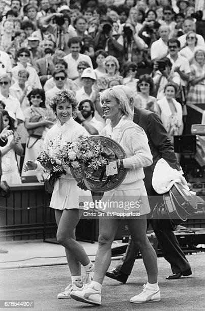 Czech born American tennis player Martina Navratilova holds the Venus Rosewater Dish trophy and a bouquet of flowers alongside the defeated Chris...