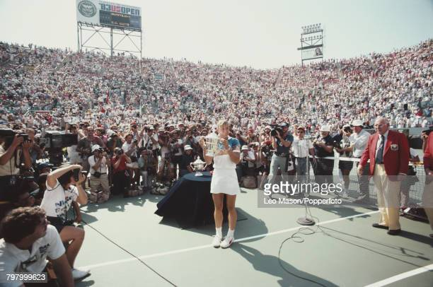 Czech born American tennis player Martina Navratilova poses with the trophy in front of photographers and spectators after winning the final of the...