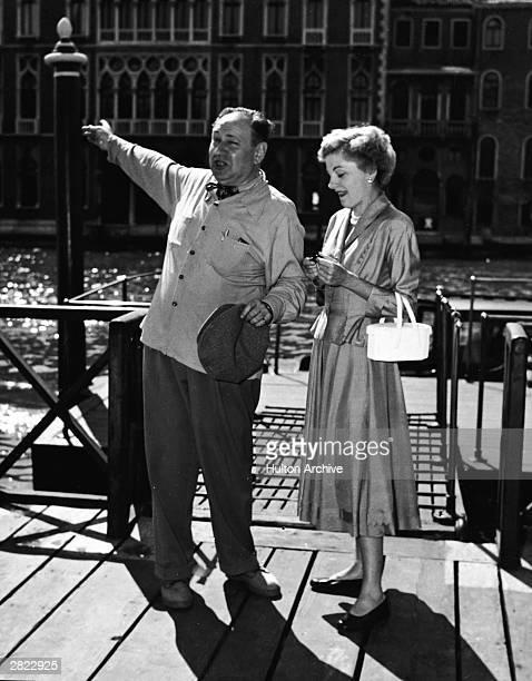 Czech born film composer and conductor Erich Korngolf points at something over his shoulder as American actor Joan Fontaine stands next him smiling...