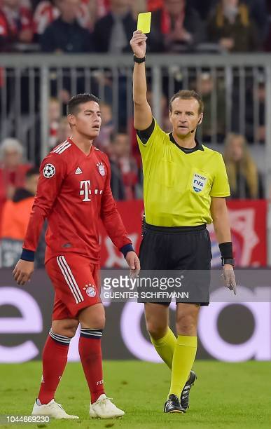 Czech eferee Pavel Kralovec shows Bayern Munich's Columbian midfielder James Rodriguez the yellow card during the UEFA Champions League Group E...