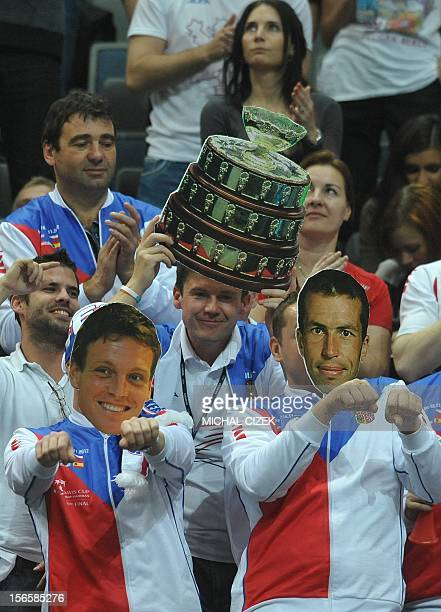Czech fans with the masks featuring Czech tennis player Radek Stepanek and Tomas Berdych cheer after they won their double tennis match against...