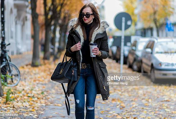 Czech fashion blogger Barbora Ondrackova holding a coffe to go in her hand wearing a parka with inner lining fur a black Proenza Schouler turtleneck...