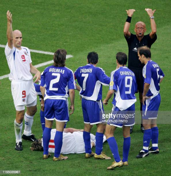 Czech forward Jan Koller and Italian referee Pierluigi Collina ask for medical help as Czech captain Pavel Nedved lies on the ground injured 01 July...