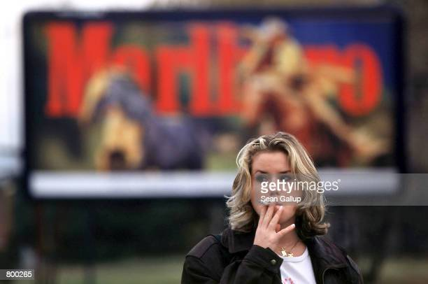 Czech girl puffs away in front of a Marlboro cigarette advertisement October 13 1997 in Prague Czech Republic Western tobacco companies see the...