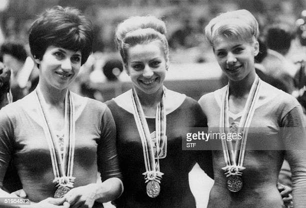 Czech gymnast Vera Caslavska winner of the gold medal in the individual beam competition smiles as she is flanked by silver medalist Tamara Manina...