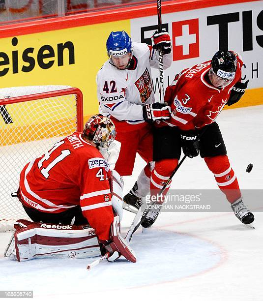 Czech Petr Koukal and Canada's Stephane Robidas vie for the puck next to goalkeeper Mike Smith during the preliminary round match Canada vs Czech...