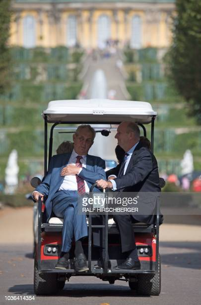 Czech President Milos Zeman and Dietmar Woidke, State Premier of the eastern federal state of Brandenburg, sit in a golf cart as they drive past...