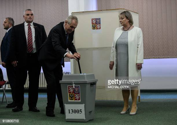 Czech President Milos Zeman is accompanied by his wife Ivana as he casts his ballot at a polling station in Prague on January 26 during the second...