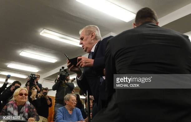 Czech President Milos Zeman is escorted by security staff as he is attacked by a woman being member of the Femen organisation on January 12 2018 at...