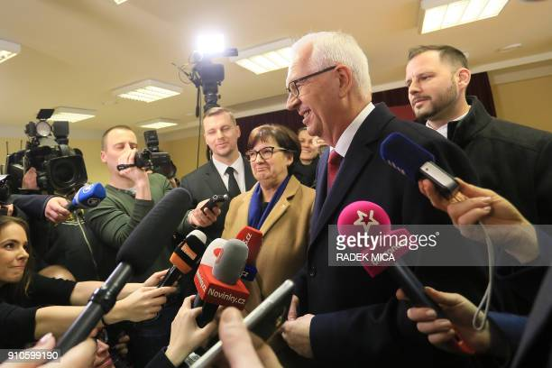 Czech presidential candidate Jiri Drahos is accompanied by his wife Eva as he speaks with journalists at a polling station in Prague's Lysolaje...