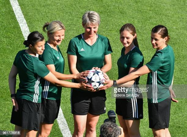 Czech referee Jana Adamkova and her assistants referees pose on the pitch before wolfsburg's training session at the Valeriy Lobanovsky Stadium in...