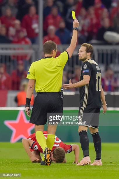 Czech Referee Pavel Kralovec shows the yellow card to Ajax Amsterdam's Dutch defender Daley Blind for a foul on Bayern Munich's German forward Thomas...