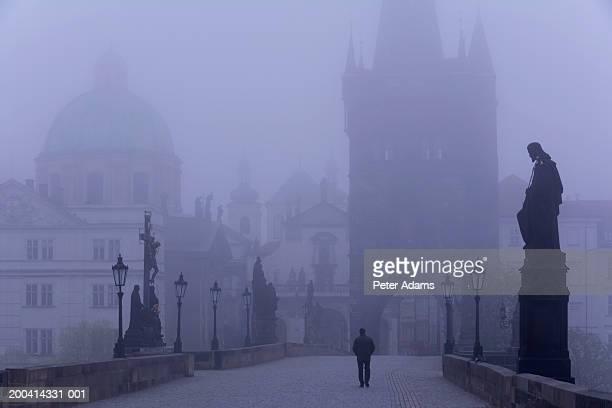 czech republic, prague, charles bridge, man walking in fog, rear view - charles bridge stock pictures, royalty-free photos & images