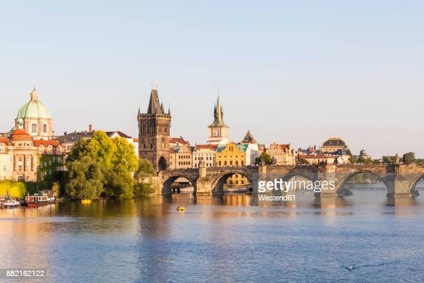 czech republic, prague, vltava and old town bridge tower on charles bridge - charles bridge stock photos and pictures