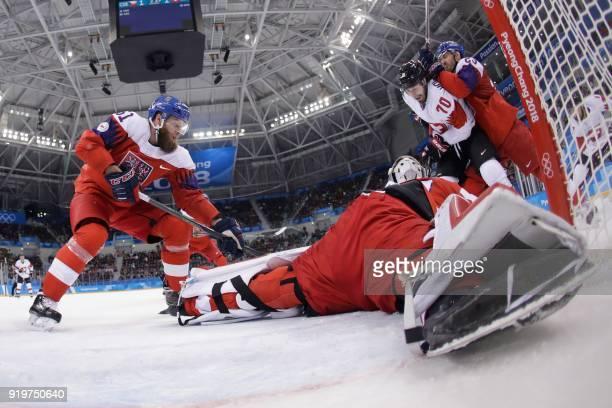 Czech Republic's Adam Polasek watches as Switzerland's Denis Hollenstein and Czech Republic's Ondrej Nemec clash in the men's preliminary round ice...