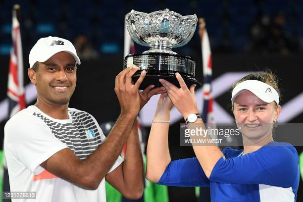 Czech Republic's Barbora Krejcikova and partner Rajeev Ram of the US pose with the championship trophy after winning their mixed doubles final match...