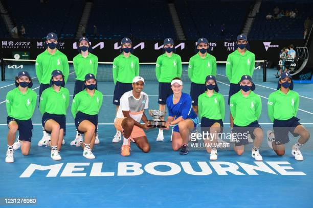 Czech Republic's Barbora Krejcikova and partner Rajeev Ram of the US pose with the championship trophy and ballkids after winning their mixed doubles...