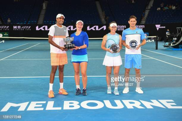 Czech Republic's Barbora Krejcikova and partner Rajeev Ram of the US pose with the championship trophy after beating Australia's Samantha Stosur and...